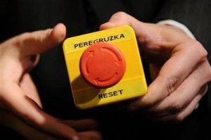 "The ""Reset Button"" given by U.S. Secretary of State Hiullary Clinton to Russian Foreign Minister Dmitri Larov to symbolize the ""resetting"" of U.S.-Russian relations. The Russian word ""Peregruzka"" printed on the button actually means ""overcharged"" or ""overload,"" not ""reset."""