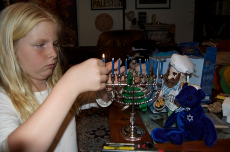 Talitha lighting the Hanukkah menorah on the first night.