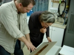 Dr. Robert Cargill and Dr. Pnina Shor read a section of a mounted Dead Sea Scroll in the IAA Conservation lab in Jerusalem.