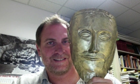 "With a replica of the ""Mask of Agamemnon"""